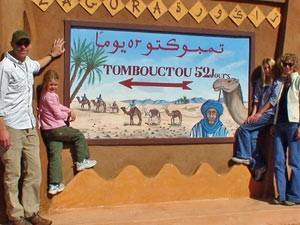 Schild am Rande der Wüste mit der Wegbeschreibung nach Timbuktu