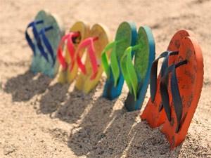 Upper Keys: Bunte Flip Flops stecken im Sand auf Islamorada
