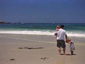Vater mit Kindern am Strand