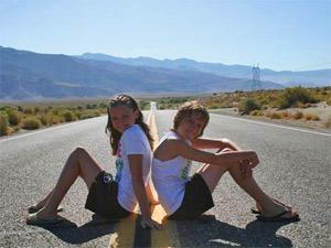 Kinder sitzen auf einer verlassenen Strasse in der USA