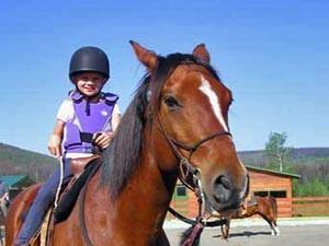 Ein Kind reitet auf einem Pferd