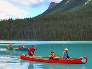Eine Familie fährt in Kanus über einen blauen See