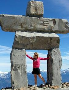 Eine Frau mit einer großen Inukshuk Figur in den Bergen