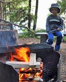 Ein Junge sitz am Lagerfeuer