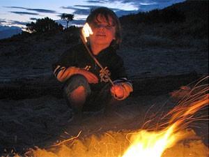 Ein Kind sitzt am Lagerfeuer und grillt Marshmallows - Kanada Rundreise mit Kindern