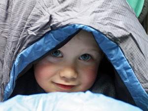 Ein Kind liegt unter einem Schlafsack - Wells Gray Provincial Park