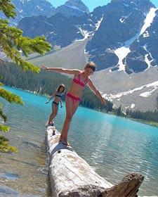 Kinder balancieren auf einem Baumstamm am See - Kanada Rundreise mit Kindern