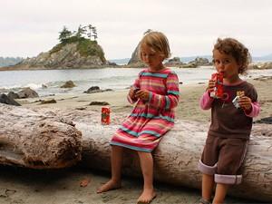 Kinder sitzen am Strand an der Sunshine Coast