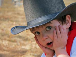 Ein kleiner Junge mit Cowboy Hut auf.