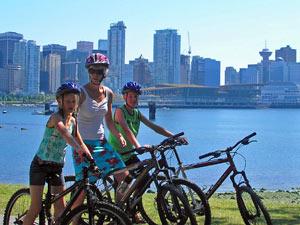 Eine Familie mit Fahrrädern vor der Skyline von Vancouver