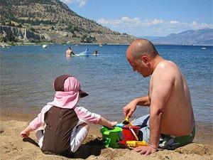 Vater und Kind spielen im Sand