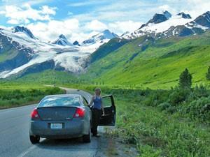 Ein Auto steht vor einer Panorama-Bergkulisse