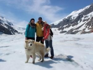 Drei Menschen und ein Hund im Schnee vor Bergkulisse