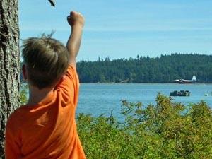 Ein Junge triumphiert vor einem See in Kanada