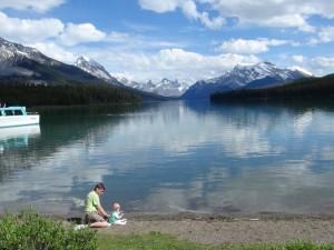 Ein Vater sitzt mit seinem Kind am See